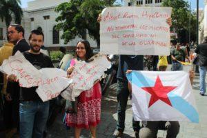 Os manifestantes mostran aos medios os cartaces rachados na porta da Asemblea.