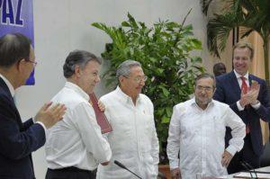 Na mesa dos acordos na Habana, Raúl, á beira do Comandante Timoleón Jimenez, chefe do Estado Maior-Geral das FARC-EP, arrodeados de Santos Calderón, presidente de Colômbia, Ban Ki-moon, secretário-geral da ONU e Borge Brende, ministro dos Negócios Estrangeiros do Reino da Noruega.